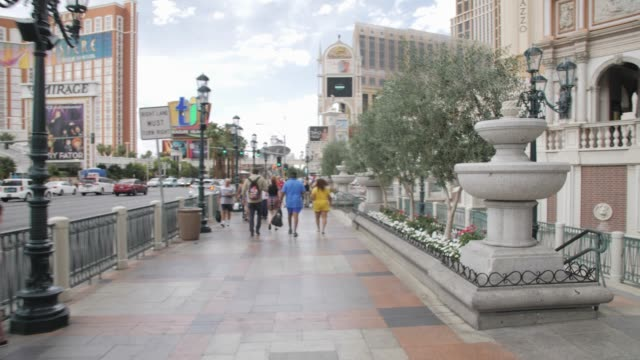 tracking shot of people walking and the venetian hotel and casino, the strip, las vegas boulevard, las vegas, nevada, usa - venetian hotel las vegas stock videos & royalty-free footage