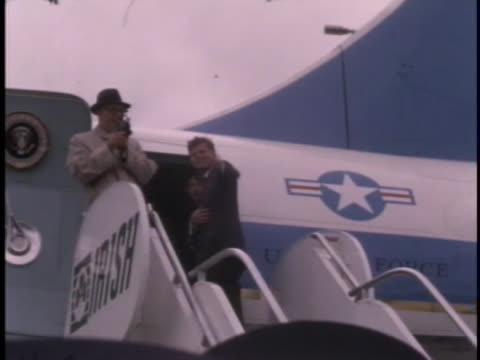 cu tracking shot of president john f kennedy as he climbs a staircase to board air force one as he reaches the top he turns around and waves to... - united states and (politics or government) stock videos & royalty-free footage