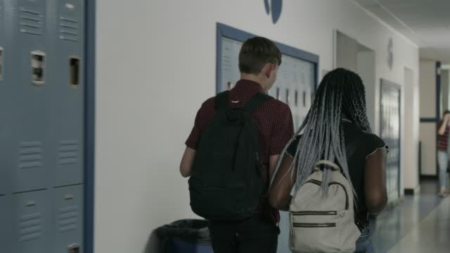 tracking shot of rear view of boy and girl walking in school corridor / provo, utah, united states - ロッカー点の映像素材/bロール