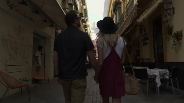 tracking shot of rear view of tourist couple admiring architecture in city / seville, sevilla, spain - europe tourist stock videos & royalty-free footage