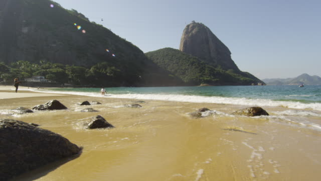 tracking shot of red beach in rio with waves washing over exposed boulders. - 2013 stock videos & royalty-free footage