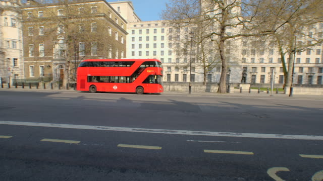 tracking shot of red double decker bus at empty whitehall during lockdown for coronavirus pandemic in london, england, uk, on thursday, april 9,... - whitehall london stock videos & royalty-free footage