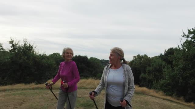 Tracking shot of senior women walking with nordic walking poles in park.