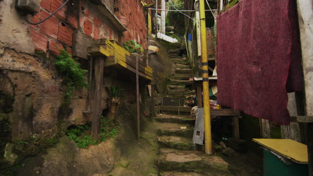 tracking shot of shanties along the stairs in a favela in rio de janeiro, brazil - slum stock-videos und b-roll-filmmaterial