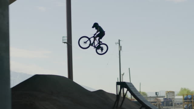 tracking shot of silhouette of boy jumping hills on bicycles beneath overpass / salt lake city, utah, united states - mountainbiking stock-videos und b-roll-filmmaterial