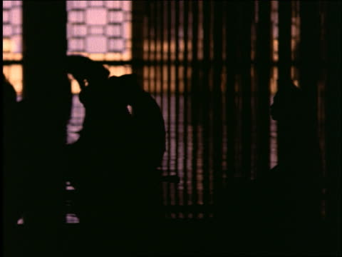 tracking shot of silhouetted men praying in Istiqual Mosque / Jakarta / Indonesia