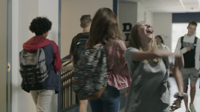 vídeos de stock, filmes e b-roll de tracking shot of silly girls singing and dancing in school corridor / provo, utah, united states - bailarina