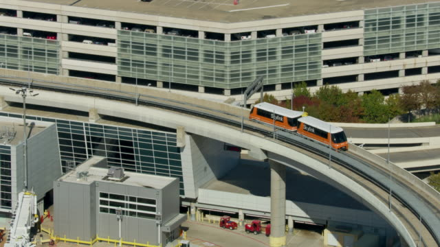 tracking shot of skylink train entering a terminal at the dallas forth worth international airport - dallas fort worth airport stock videos & royalty-free footage