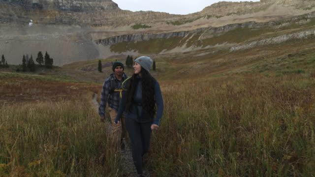 tracking shot of smiling couple hiking on mountain trail / mount timpanogos, utah, united states - approaching stock videos & royalty-free footage