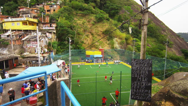 vidéos et rushes de rio de janeiro, brazil - june 23: tracking shot of soccer game to scenic view of a favela - brésil