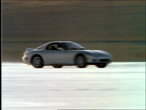 tracking shot of sports car driving fast, swerving + spinning /desert