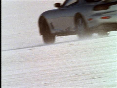 tracking shot of sports car driving + sliding in desert