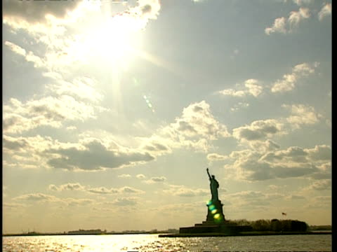 wa tracking shot of statue of liberty silhouetted against sunny sky, new york - sunny video stock e b–roll