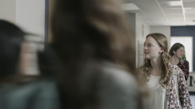tracking shot of teacher and student walking and talking in school corridor / provo, utah, united states - ロッカー点の映像素材/bロール