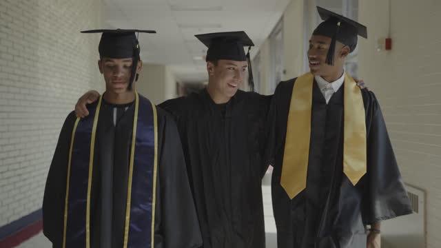 tracking shot of teenage boys graduating from high school celebrating in corridor / springville, utah, united states - springville utah stock videos & royalty-free footage