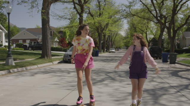 tracking shot of teenage girls dancing on roller skates in neighborhood street / salt lake city, utah, united states - singing stock videos & royalty-free footage
