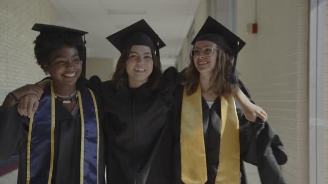 tracking shot of teenage girls graduating from high school celebrating in corridor / springville, utah, united states - springville utah stock videos & royalty-free footage