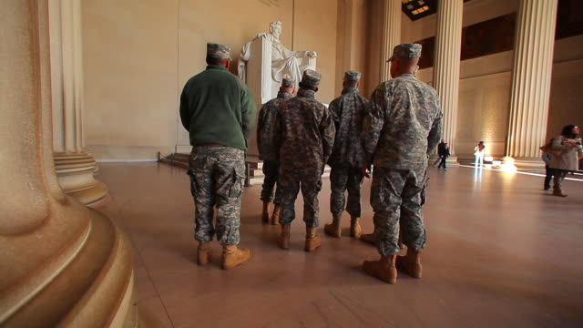 a tracking shot of the back of a group of soldiers who are looking at the lincoln memorial. - lincolndenkmal stock-videos und b-roll-filmmaterial