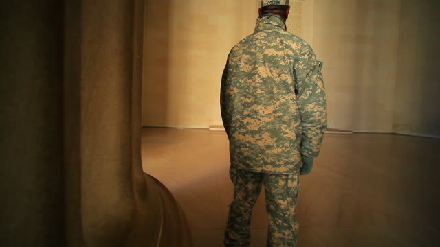 A tracking shot of the back of a single soldier who is gazing at the constitution.