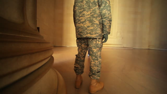 A tracking shot of the back of a single soldier who is intently gazing at the constitution.