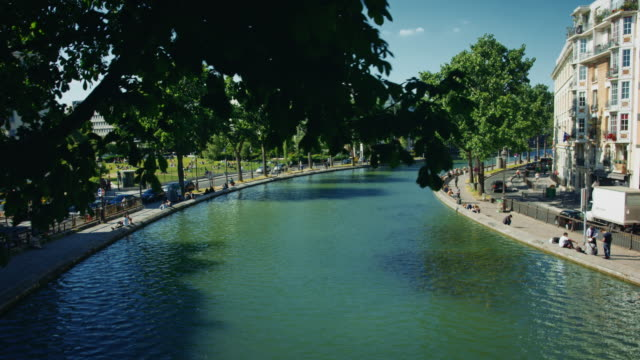 vidéos et rushes de tracking shot of the canal saint-martin from a pedestrian bridge - dolly shot