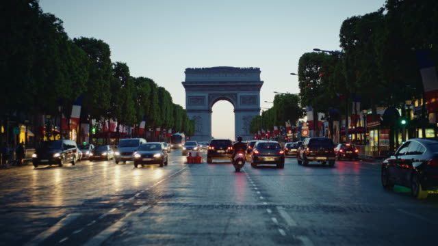 Tracking shot of the Champs-Elysées avenue, french flags decorated, looking at the Arch of Triumph, at dusk
