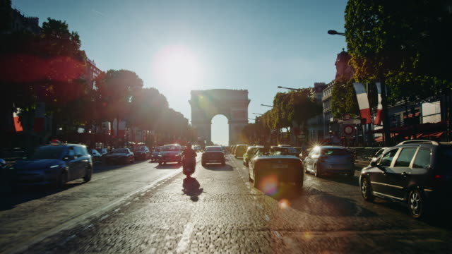 tracking shot of the champs-elysées avenue, french flags decorated - triumphbogen paris stock-videos und b-roll-filmmaterial