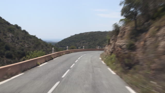 vidéos et rushes de a tracking shot of the curvy road with hilly landscape and blue sky in the background - route de montagne