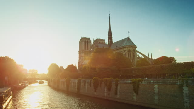 tracking shot of the east side of notre-dame de paris and banks of the seine river at sunset - back lit stock videos & royalty-free footage