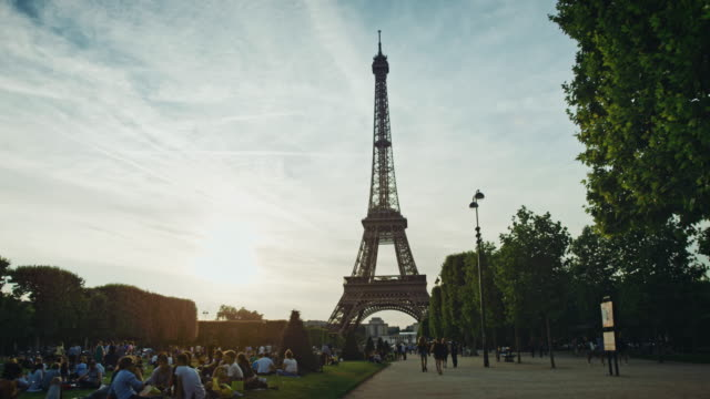 tracking shot of the eiffel tower as seen from the champ-de-mars at sunset - eiffel tower stock videos & royalty-free footage