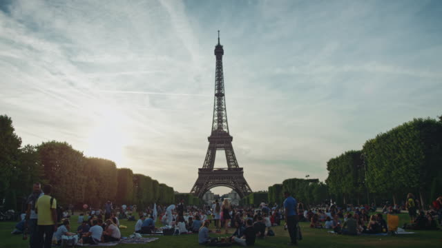 Tracking shot of the Eiffel tower from the Champ-de-Mars at sunset, people sitting on the lawn