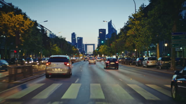 tracking shot of the grande-armée avenue, looking at the défense district skyline, at dusk - autoperspektive stock-videos und b-roll-filmmaterial