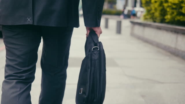 tracking shot of the laptop suitcase while businessman is walking in the street - laptop bag stock videos and b-roll footage