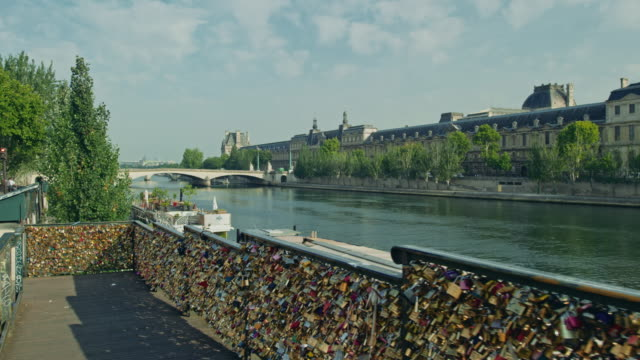 tracking shot of the louvre and banks of the seine river from the pont des arts, with love padlocks in the foreground - romance stock videos & royalty-free footage