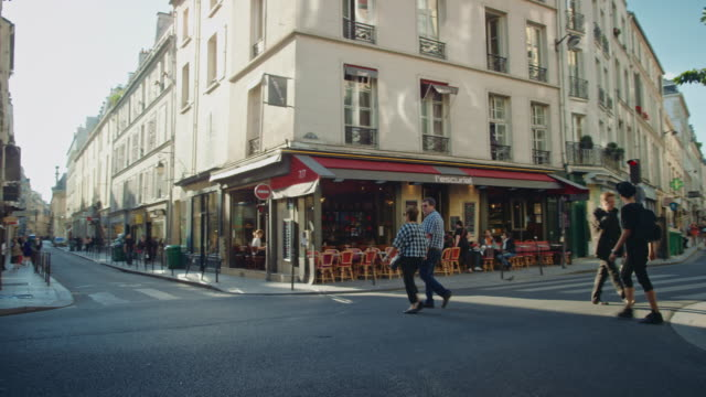 Tracking shot of the Marais historical streets, cars, people walking by