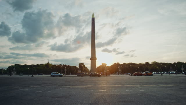 Tracking shot of the Place de la Concorde obelisk at sunset, cars passing by