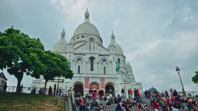tracking shot of the sacré-coeur basilica of montmartre, tourists sitting on stairs - basilique du sacre coeur montmartre stock videos & royalty-free footage