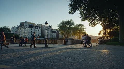 tracking shot of the seine river banks at sunset, people walking and bicycle passing by - large group of people stock videos & royalty-free footage
