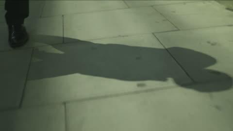vídeos y material grabado en eventos de stock de tracking shot of the shadow of a man as he strolls over wide grey paving stones in smart shoes in london, uk. - sombra