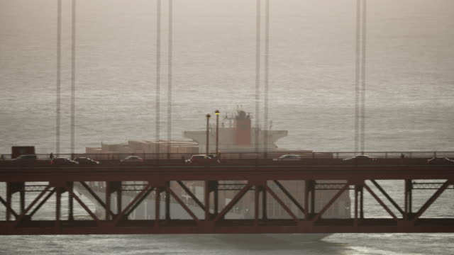 Tracking shot of the traffic on the Golden Gate Bridge with a container ship in the background at sunset