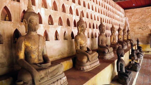 vidéos et rushes de travelling de milliers de statues de bouddha au wat si saket, vientiane, laos - assis en tailleur