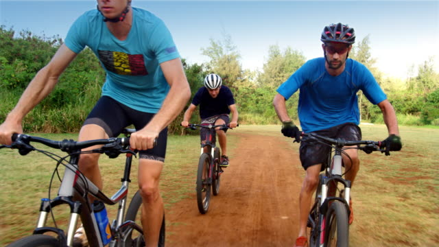 tracking shot of three people racing through field on mountain bikes - turtle bay hawaii stock videos and b-roll footage