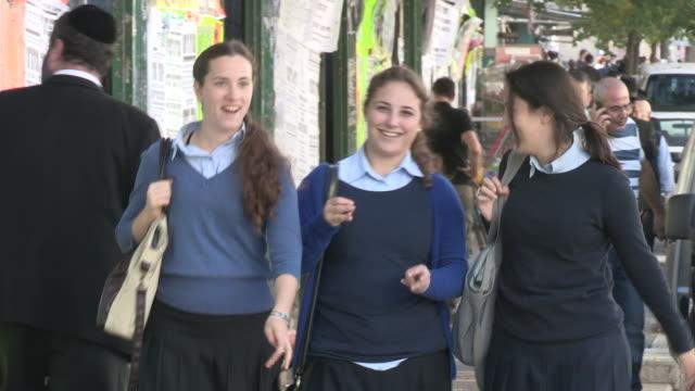 tracking shot of three teenage israeli girls on a busy sidewalk - skull cap stock videos & royalty-free footage
