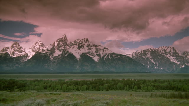 tracking shot of time lapse clouds in blue sky over mountains and plains / Tetons (Rocky Mtns) / Wyoming