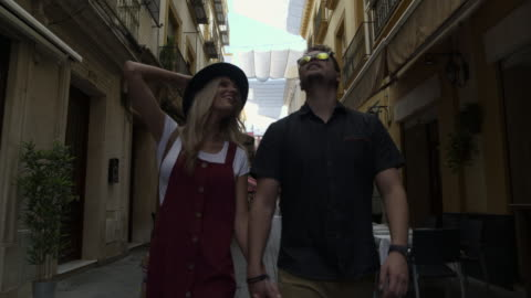 tracking shot of tourist couple admiring architecture in city / seville, sevilla, spain - cobblestone stock videos & royalty-free footage