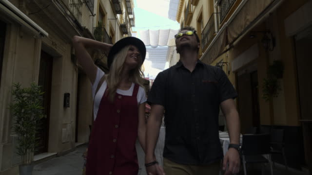 tracking shot of tourist couple admiring architecture in city / seville, sevilla, spain - europe stock videos & royalty-free footage
