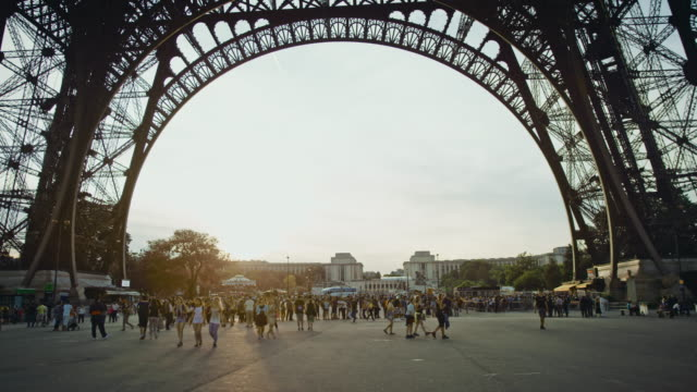 Tracking shot of tourists in line under the Eiffel tower at sunset