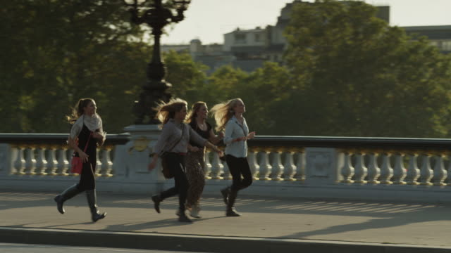 Tracking shot of tourists running on Paris bridge / Paris, France