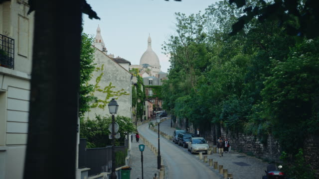 tracking shot of typical montmartre streets, sacré-coeur basilica in the background - basilique du sacre coeur montmartre stock videos & royalty-free footage