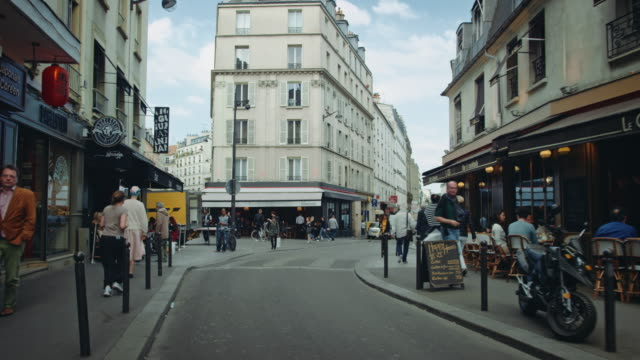 tracking shot of typical paris streets, with bars and cafés, people walking by - paris bildbanksvideor och videomaterial från bakom kulisserna